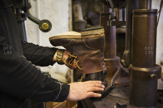 Close up of worker in a shoemaker's workshop, using a machine to make a leather ankle boot