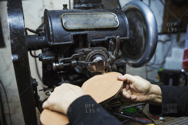 Close up of worker in a shoemaker's workshop, using a machine to sew a leather sole