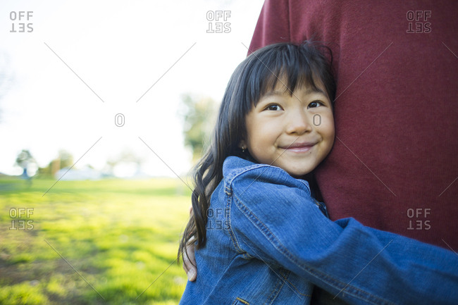 Cute little girl smiling while embracing father at park