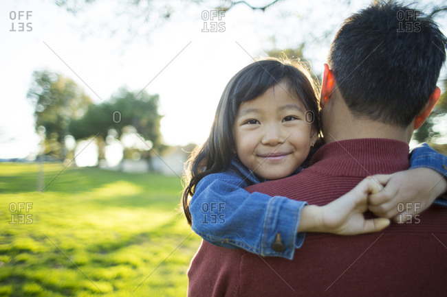 Portrait of cute girl smiling while carried by father in park