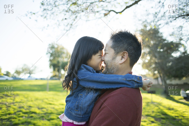 Side view of playful father and daughter rubbing noses at park