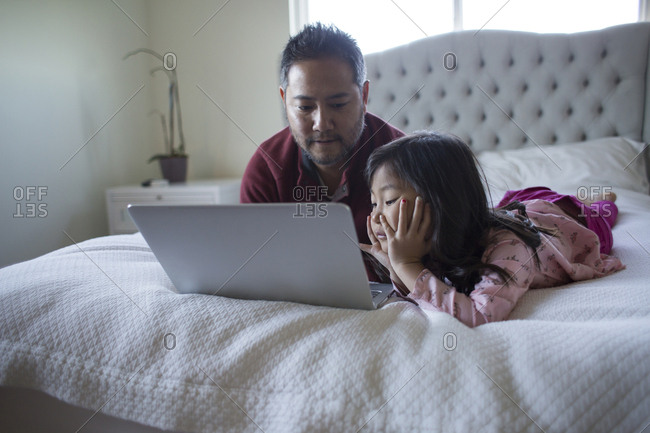 Mature man using laptop with cute daughter while lying on bed at home