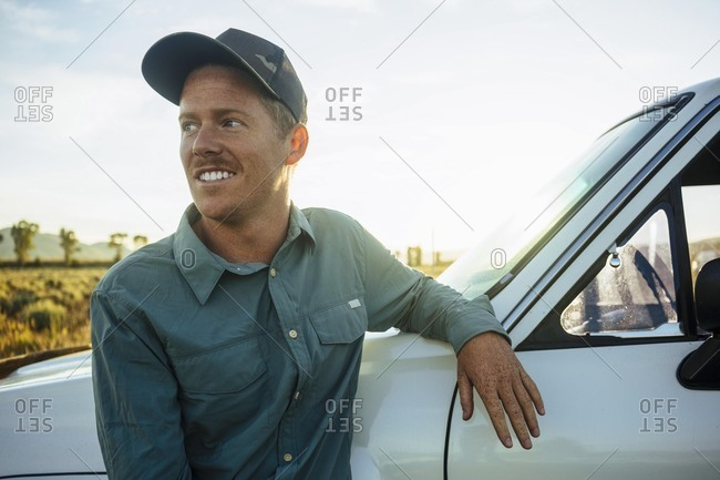 Smiling young man wearing baseball cap leaning against truck