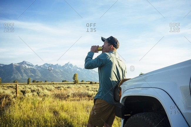 Side view of young man drinking beer while leaning against white truck