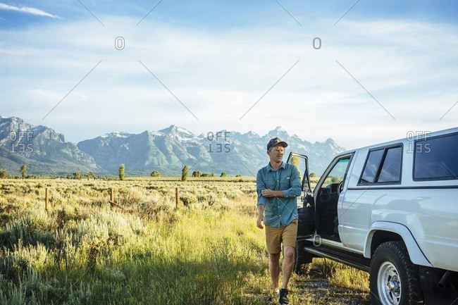 Young man walking by car with mountains in background at Grand Teton National Park