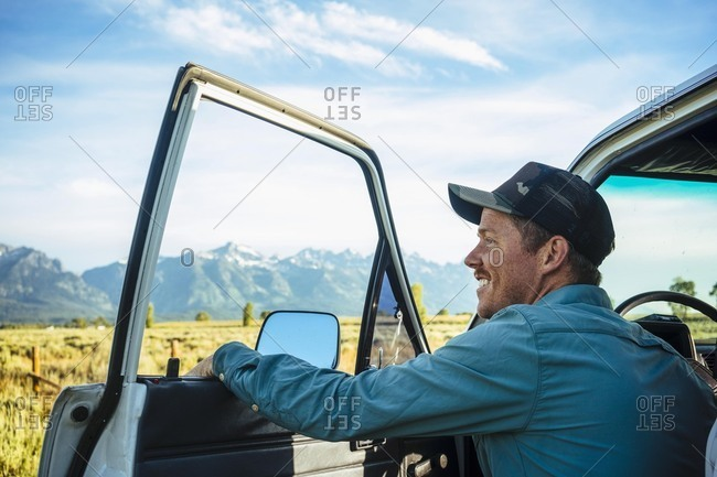 Young male tourist by car sightseeing at Grand Teton National Park