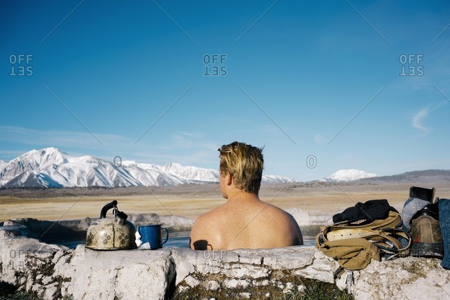 Rear view of young man relaxing in natural  hot spring near Mammoth Lakes