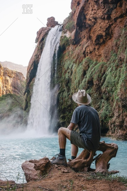 Rear view of young male tourist looking at Havasu Falls in Grand Canyon National Park