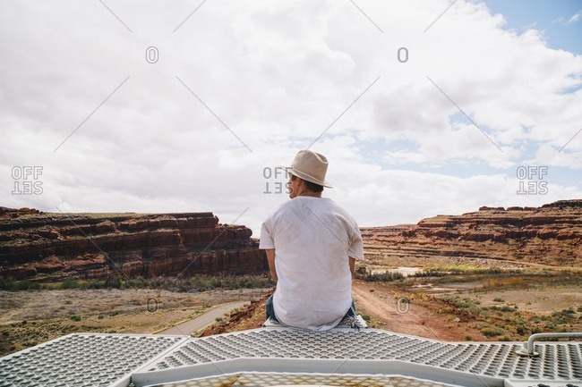 Rear view of young man looking at rock formations at Moab against cloudy sky