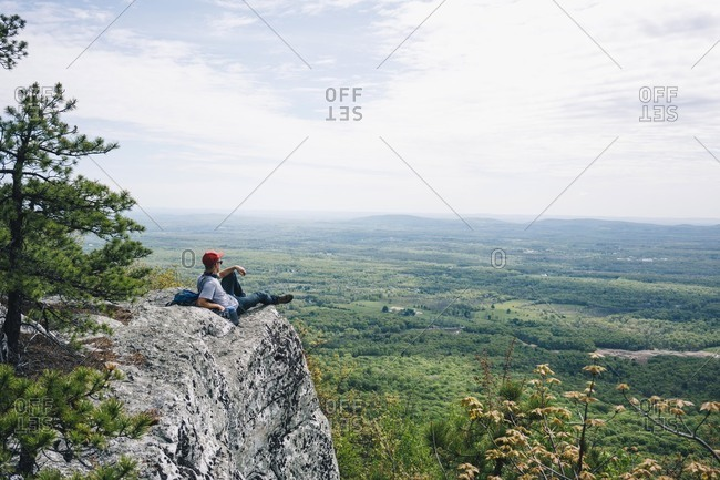 Young male hiker relaxing on mountain cliff against sky