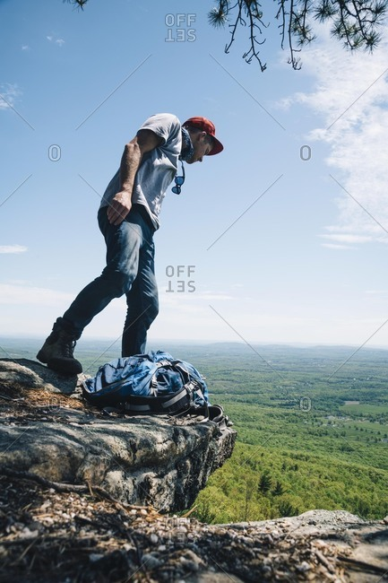 Full length of male backpacker looking down from edge of cliff against sky