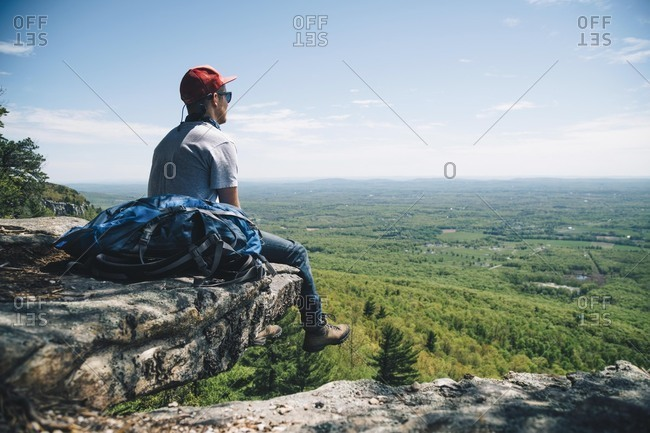 Full length of male backpacker sitting on edge of cliff against sky