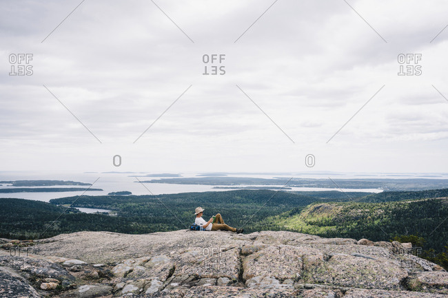 Relaxed male backpacker reading book on mountain at Acadia National Park against sky