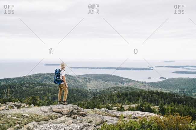 Full length of backpacker looking at ocean view from mountain at Acadia National Park