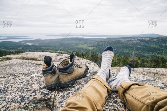 Male hiker relaxing on rocky mountain overlooking Acadia National Park