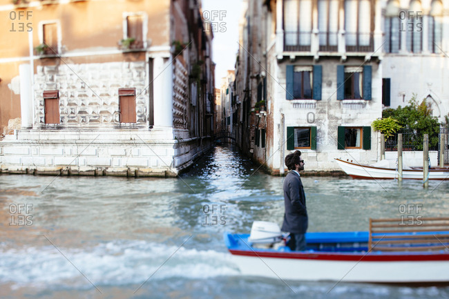 Venice, Italy - May 8, 2010: Man in a business suit standing in a moving motorboat commuting to work in Venice Italy