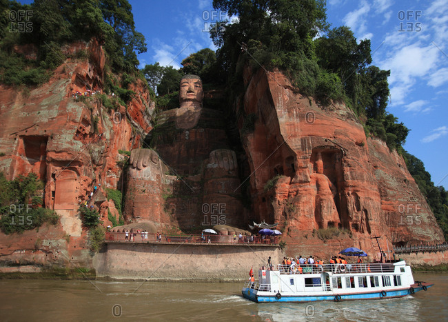 Leshan, China - September 14, 2011: Leshan giant Buddha with tour boat passing by