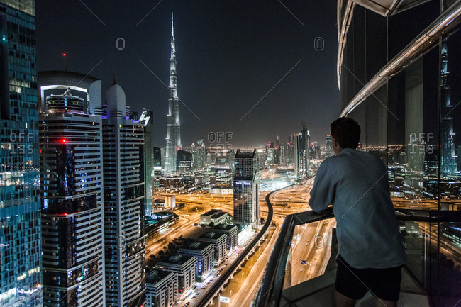Dubai, United Arab Emirates - October 13, 2014: A person is watching the breathtaking skyline, which is located on the southeast coast of the Persian Gulf and the most populous city and emirate in the United Arab Emirates