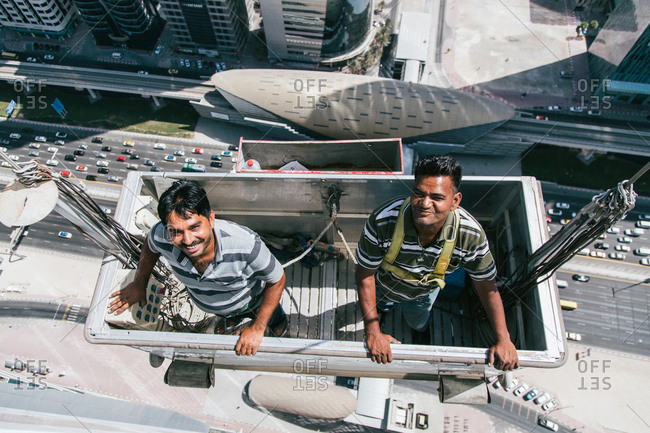 Dubai, United Arab Emirates - October 14, 2014: Two smiling workers are dangling from a tall building