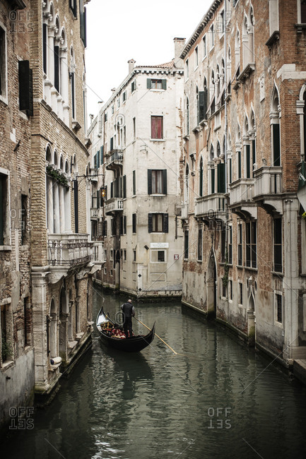 Venice, Italy - April 1, 2016: A gondolier is rowing his boat in the channels of Venice. Gondola ride tours are very popular among tourists