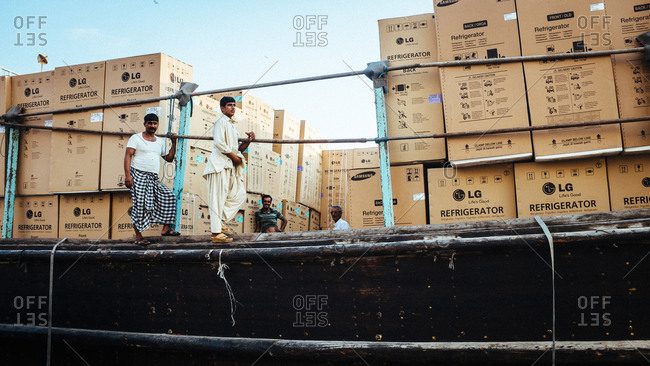 Dubai, United Arab Emirates - November 18, 2013: Two smiling workers on a ship with refrigerators from LG Electronics