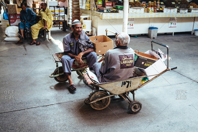 Dubai, United Arab Emirates - November 18, 2013: Two men sitting on a wheelbarrow