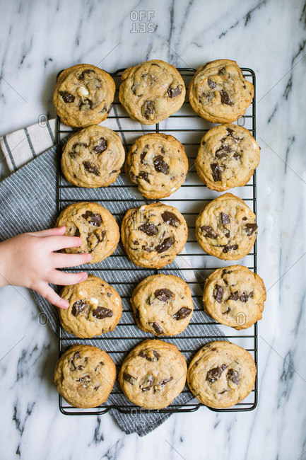 Child's hand reaching for freshly baked chocolate chip cookies