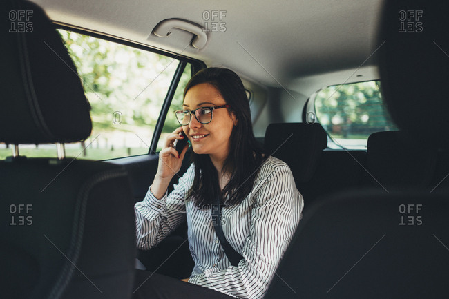Woman making phone call in back seat of car