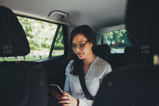 Woman checking smartphone in back seat of car