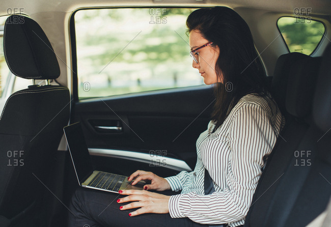Woman using laptop in back of car