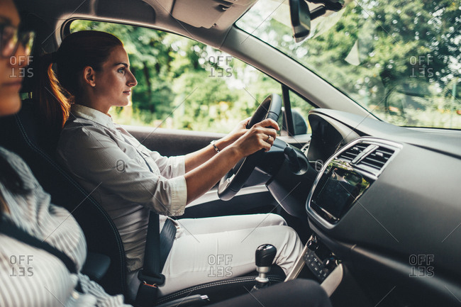 Woman driving a car with friend in front seat