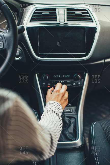 Woman's hand on stick shift of automobile