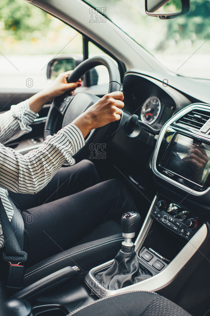 Woman driving a car on with manual transmission