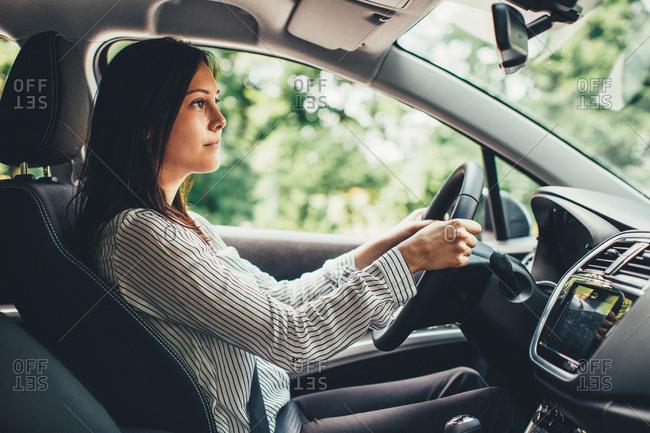 Woman checking rear view mirror in car