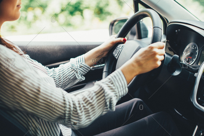 Close-up of woman's hands on steering wheel of car