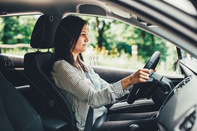 Smiling young woman driving a car