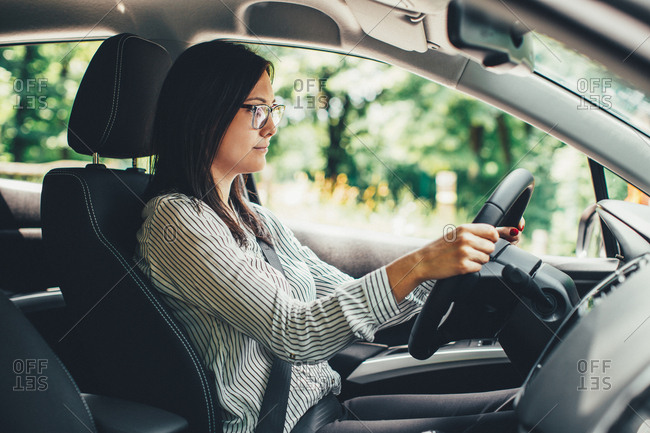 Woman in glasses driving a car