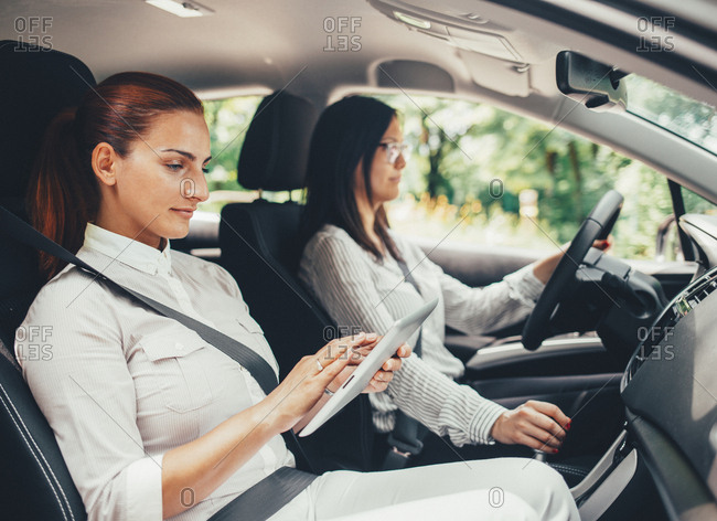 Woman driving while front seat passenger uses tablet