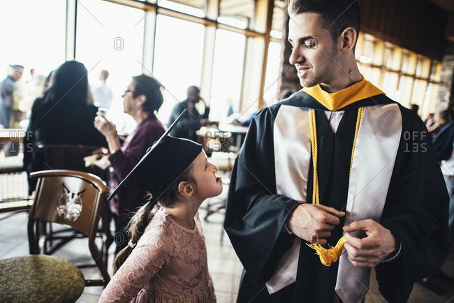 Girl making face at graduating man