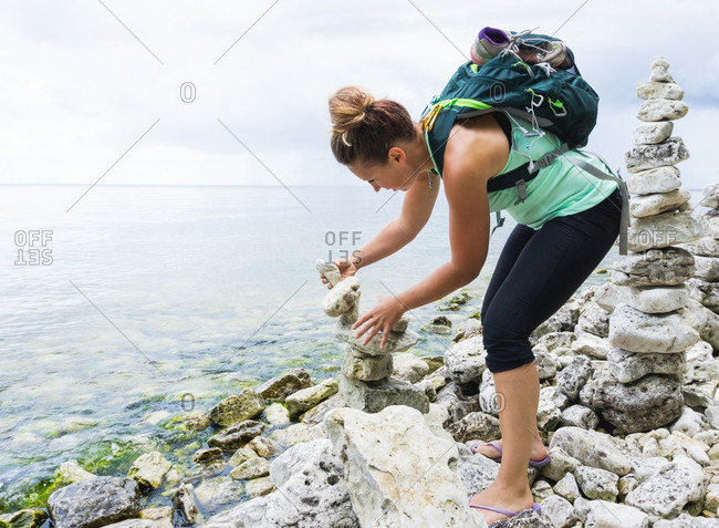 Woman stacking rocks along the shore at Cave Point County Park, Wisconsin