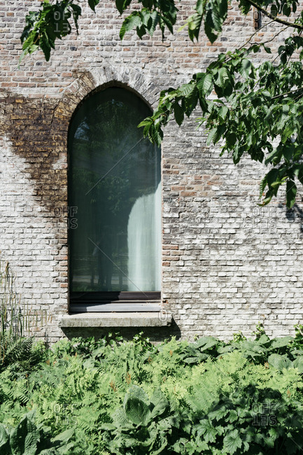 Arched window of Kanaal, a place designed by Alex Vervordt in Antwerp, Belgium