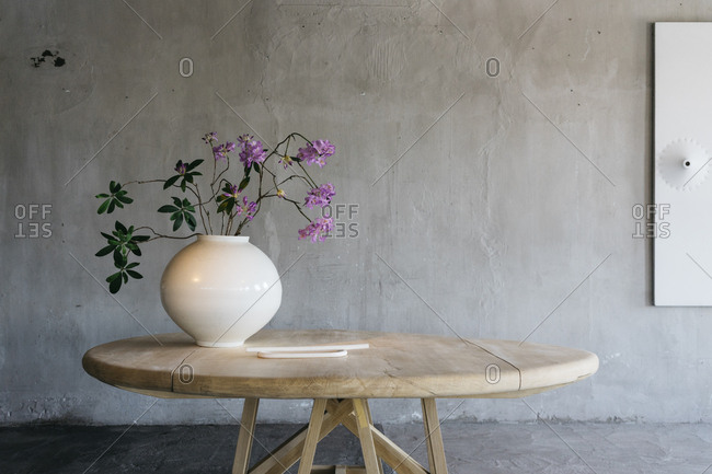 Round vase with pink flowers on a wooden table