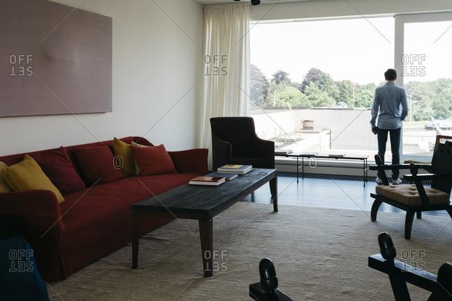 Antwerp, Belgium - June 2, 2017: Man in a living room in a home in Kanaal development in Antwerp, Belgium