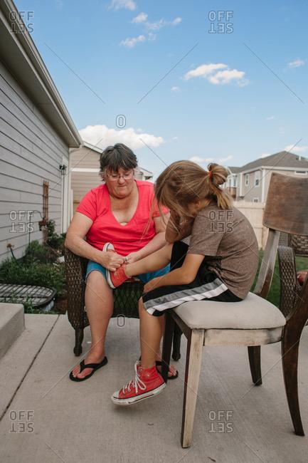 Woman helping boy tie shoe on patio