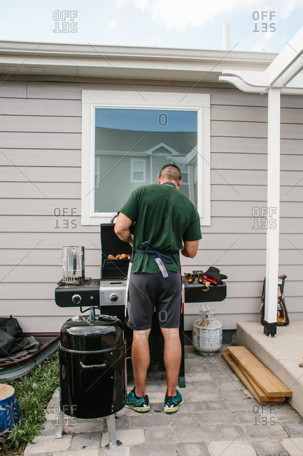 Man cooking at grill outside house