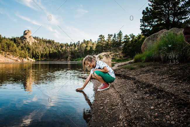 Boy touching a lake surface