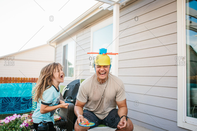 Dad and boy laughing with silly hat