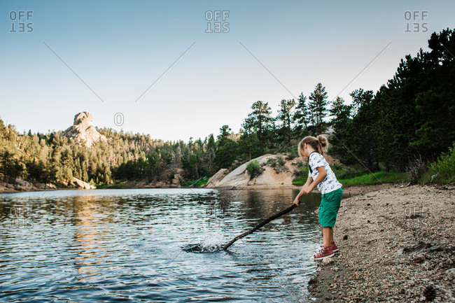Boy splashing in lake with stick