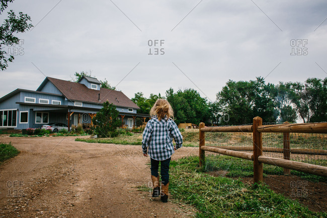 Boy walking towards country home