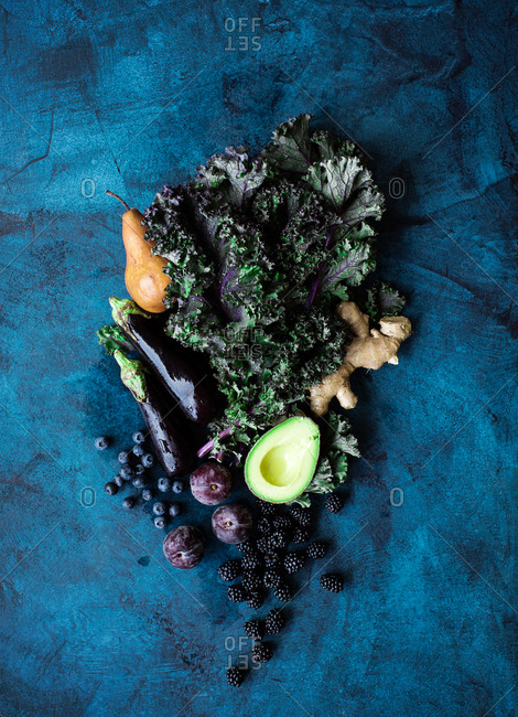 Raw fruits and veggies on dark background